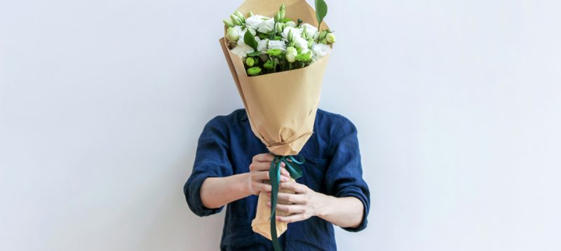 Man holding bouquet of flowers for blog about the softer side of M&A, customer and employee relations